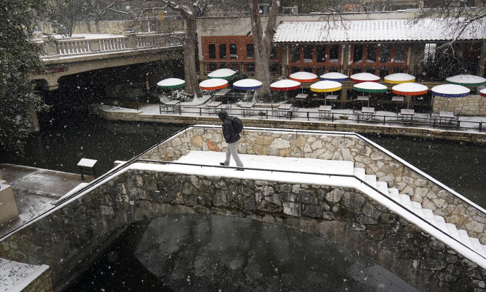A man crosses a bridge along the River Walk as snow falls, Thursday, Feb. 18, 2021, in San Antonio. Snow, ice and sub-freezing weather continue to wreak havoc on the state's power grid and utilities. (AP Photo/Eric Gay)