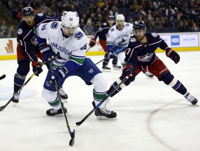 Vancouver Canucks forward Tim Schaller, center, chases the puck between Columbus Blue Jackets defenseman Seth Jones, left, and forward Brandon Dubinsky during the first period of an NHL hockey game in Columbus, Ohio, Tuesday, Dec. 11, 2018. (AP Photo/Paul Vernon)