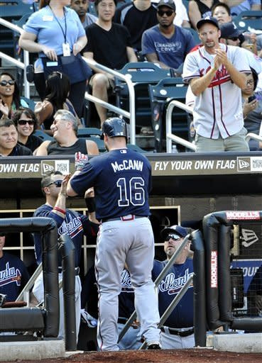 Atlanta Braves' Brian McCann is greeted at the dugout by teammates after hitting a solo home run off of New York Mets' Chris Young in the sixth inning of a baseball game, Sunday, Sept. 9, 2012, at Citi Field in New York. (AP Photo/Kathy Kmonicek)