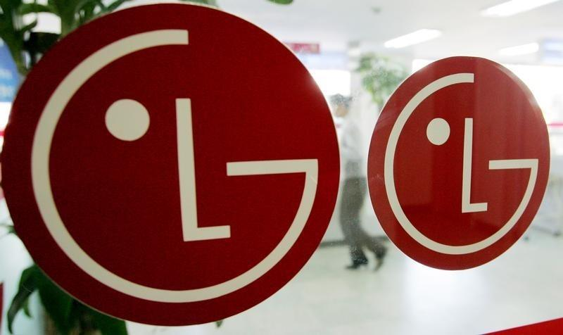 An employee of LG Electronics walks behind company logos at a branch in Seoul.