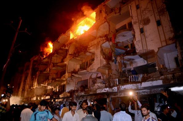 People gather on the site of bomb blast in Karachi on March 3, 2013. A bomb attack in Pakistan's largest city Karachi on Sunday killed at least 23 people, including women and children, and wounded 50 others, police said. AFP PHOTO/ASIF HASSAN        (Photo credit should read ASIF HASSAN/AFP/Getty Images)