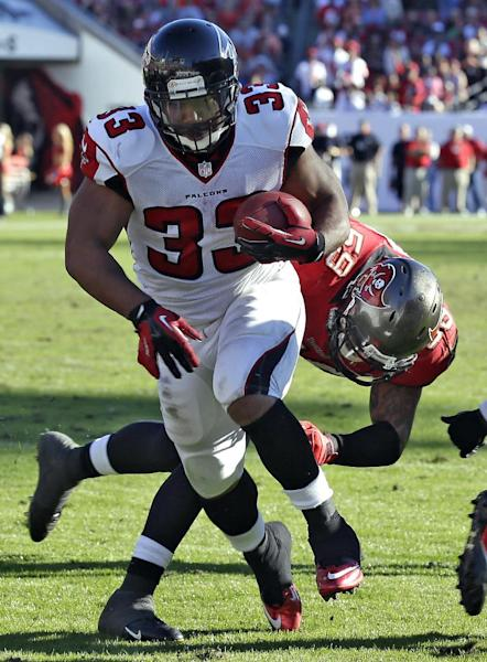 Atlanta Falcons running back Michael Turner (33) gets past Tampa Bay Buccaneers middle linebacker Mason Foster (59) to score what proved to be the game-winning touchdown during the fourth quarter of an NFL football game on Sunday, Nov. 25, 2012, in Tampa, Fla. The Falcons defeated the Buccaneers 24-23. (AP Photo/Chris O'Meara)