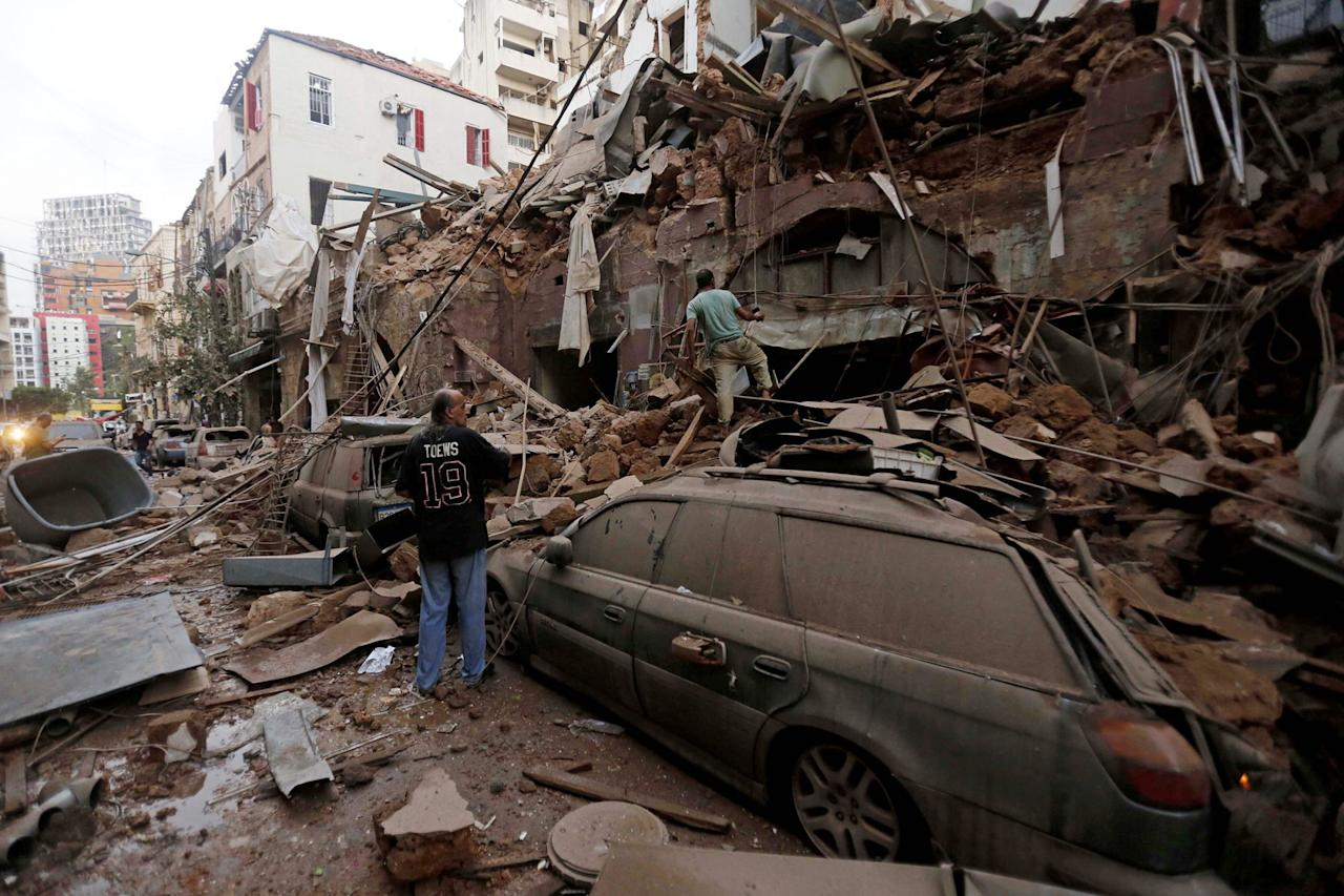 <p>People search through the rubble of buildings and cars following the massive blast.</p>