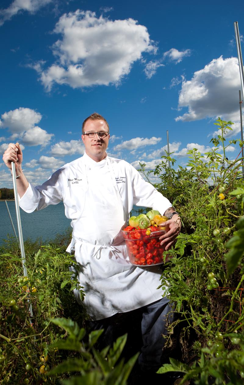 Head Chef for the Blue Water Grill, Michael-Patrick McCann, poses in the vegetable garden that has replaced sthe restaurant's landscaping.  Vegetables and herbs are picked and cooked with daily.  (AP Photo/Adam Bird)