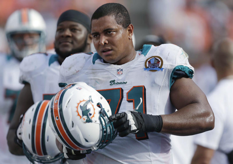 In this Dc. 16, 2012, photo, Miami Dolphins tackle Jonathan Martin (71) stands on the sidelines during the Dolphins' NFL football game against the Jacksonville Jaguars in Miami. Martin, the offensive tackle at the center of the Dolphins' bullying scandal, has been traded to the San Francisco 49ers. The Dolphins announced the deal Tuesday night, March 11, 2014, on the first day of NFL free agency. Martin's move cross country brings him back to the Bay Area to be reunited with his former Stanford coach, Jim Harbaugh. (AP Photo/Wilfredo Lee)
