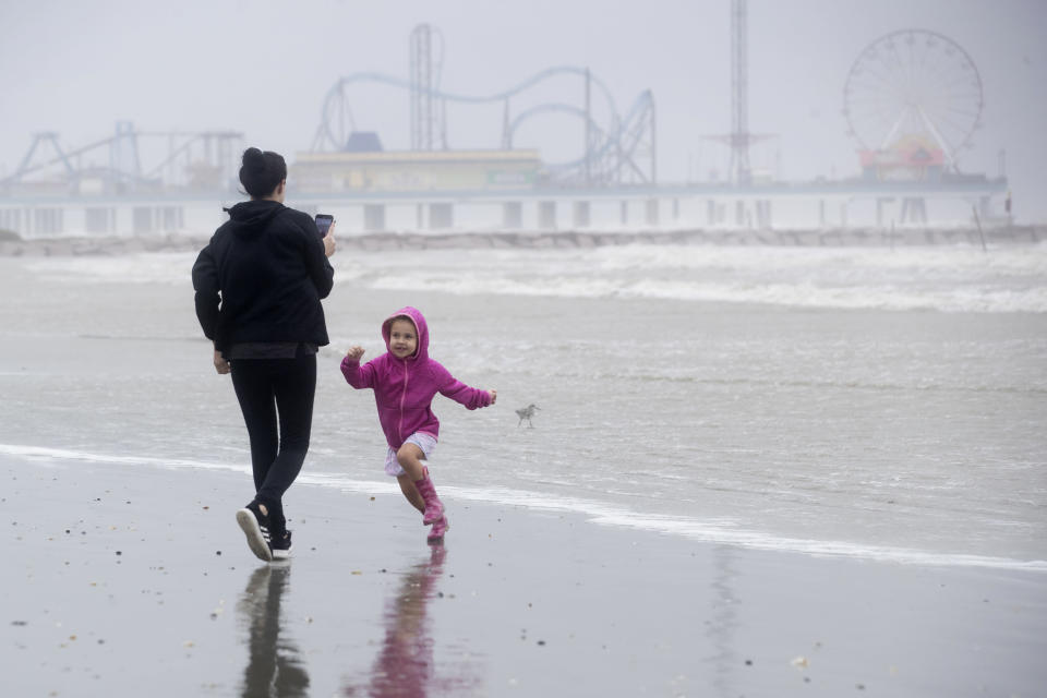 Brittany Griffin walks on the beach with her daughter, June, 3, as they watch the rough surf churned up by Tropical Storm Beta Monday, Sept. 21, 2020, in Galveston, Texas. (Brett Coomer/Houston Chronicle via AP)