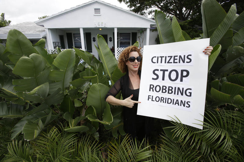 In this Monday, May 27, 2013 photo, Nancy Loft Powers poses with a sign she made in front of her home in Deerfield Beach, Fla. Powers had to sell other properties she owned because she could no longer afford the insurance.  From Cape Cod to Texas, rates for coverage against tropical storms have risen sharply since 2003, financially pinching homeowners and sparking outrage as insurance companies report profits that are higher in many coastal areas than inland for homeowners insurance. (AP Photo/Wilfredo Lee)