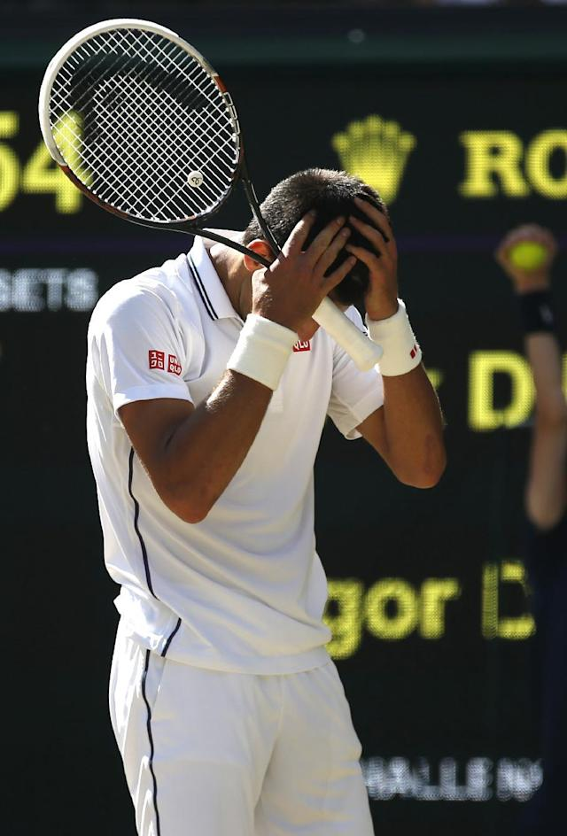 Novak Djokovic of Serbia puts his hands on his head during the men's singles semifinal match against Grigor Dimitrov of Bulgaria at the All England Lawn Tennis Championships in Wimbledon, London, Friday, July 4, 2014. (AP Photo/Pavel Golovkin)