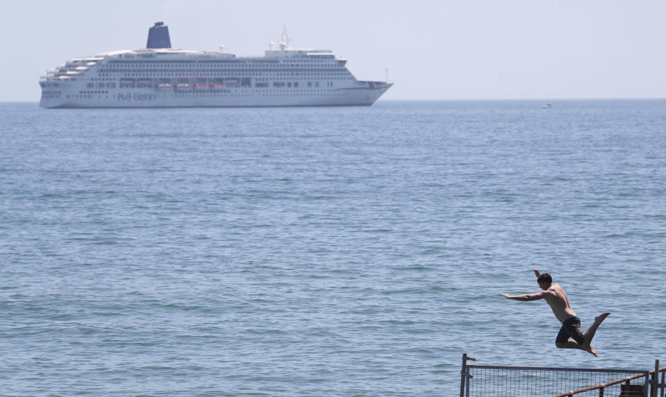 A man jumps into the sea from Bournemouth Pier, in Bournemouth, England, Thursday June 25, 2020. According to weather forecasters this could be the UK's hottest day of the year, so far, with scorching temperatures forecast to rise even further. (Andrew Matthews/PA via AP)