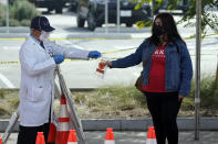 A technician distributes a test kit at a COVID-19 walk-up testing site on the Martin Luther King Jr. Medical Campus Thursday, Jan. 7, 2021, in Los Angeles. (AP Photo/Marcio Jose Sanchez)