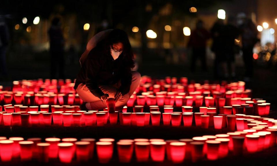 A woman lights candles in Guatemala City in honor of the people who have died from coronavirus.