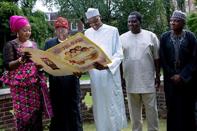 Buhari shown with a Get Well card, surrounded by aides in London on August 12 (AFP Photo/BAYO OMOBORIOWO)