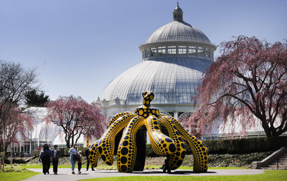 People walk by one of Yayoi Kusama's pumpkin sculptures at the New York Botanical Garden, Thursday, April 8, 2021 in New York. The expansive exhibit has opened, and ticket sales have been brisk in a pandemic-weary city hungry for more outdoor cultural events. (AP Photo/Mark Lennihan)