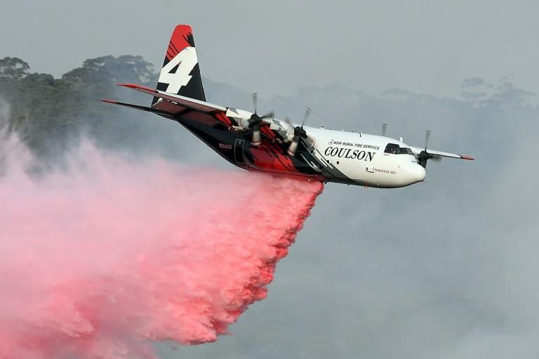 A C-130 Hercules plane from the New South Wales Rural Fire Service dropping fire retardent on bushfires