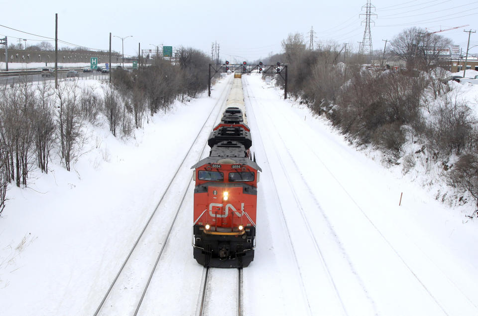 A Canadian National Railway train travels eastward on a track in Montreal, February 22, 2015. Canadian National Railway said on Sunday it is meeting with Unifor, the union representing 4,800 of its mechanical, clerical and intermodal staff, and hoped to reach a negotiated settlement or an agreement to enter binding arbitration over their contract dispute. Canada's No. 1 railway had called for binding arbitration on Friday when it first announced it was preparing to lock out employees represented by the union, a move it said could come as soon as Monday. REUTERS/Christinne Muschi (CANADA - Tags: BUSINESS EMPLOYMENT TRANSPORT)