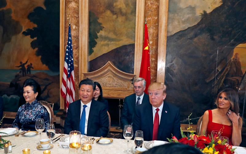 President Donald Trump and Chinese President Xi Jinping, with their wives, first lady Melania Trump and Chinese first lady Peng Liyuan are seated during a dinner at Mar-a-Lago - Credit: AP