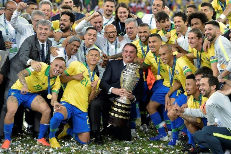 President Jair Bolsonaro holds the Copa America trophy on July 7, 2019 after Brazil defeated Peru in the tournament final