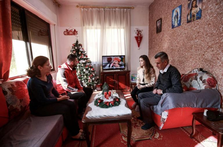 Saad Polus Qiryaqoz and his family prepare to celebrate Christmas in Jordan away from his native Iraq which they fled after jihadists seized their hometown and destroyed it six years ago but they say the feast is not the same as back home