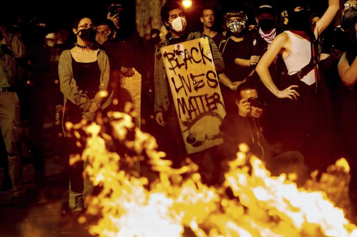 A protester holds a Black Lives Matter sign amid a crowd of people in front of a fire at the federal courthouse in Portland