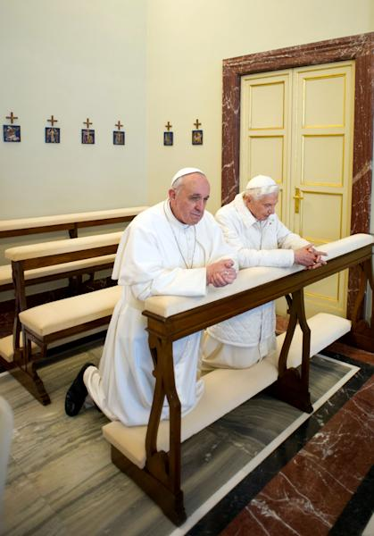 """In this photo provided by the Vatican paper L'Osservatore Romano, Pope Francis, left, and Pope emeritus Benedict XVI pray together in Castel Gandolfo Saturday, March 23, 2013. Pope Francis has traveled to Castel Gandolfo to have lunch with his predecessor Benedict XVI in a historic and potentially problematic melding of the papacies that has never before confronted the Catholic Church. The Vatican said the two popes embraced on the helipad. In the chapel where they prayed together, Benedict offered Francis the traditional kneeler used by the pope. Francis refused to take it alone, saying """"We're brothers,"""" and the two prayed together on the same one. (AP Photo/Osservatore Romano, HO)"""