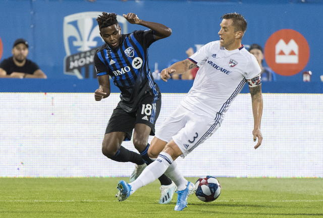Montreal Impact's Orji Okwonkwo, left, challenges FC Dallas' Reto Ziegler during first-half MLS soccer match action in Montreal, Saturday, Aug. 17, 2019. (Graham Hughes/The Canadian Press via AP)