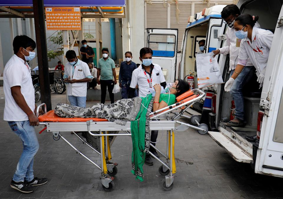 <p>A patient is wheeled inside a Covid-19 hospital for treatment in Ahmedabad on Wednesday</p> (REUTERS)