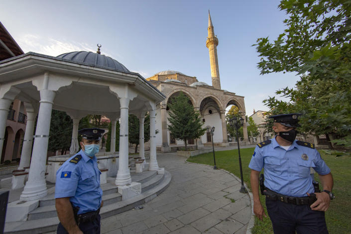 Kosovo police officers stand outside the Sultan Mehmet Fatih mosque in Pristina, Kosovo, Friday, July 31, 2020. Government measures banned all public gatherings including religious due to fear of recent uprise in COVID-19 cases. (AP Photo/Visar Kryeziu)
