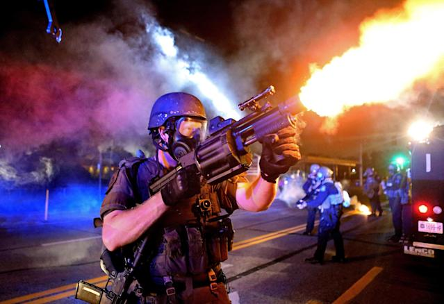 <p>A member of the St. Louis County Police tactical team fires tear gas into a crowd of people in response to a series of gunshots fired at the police during demonstrations along W. Florissant Road near the QuikTrip on August 18, 2014 in Ferguson, Missouri. Protesters also threw bottles and rocks with at least one rock striking an officer in the arm. Protesters and police clashed almost nightly for more than 2 weeks during the unrest that followed white police officer Darren Wilson shooting and killing unarmed 18-year-old Michael Brown. (David Carson/St Louis Post-Dispatch/ZUMAPRESS.com) </p>
