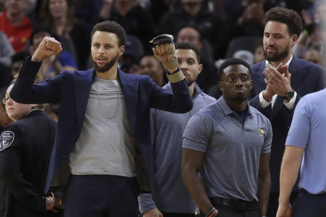 Injured Golden State Warriors guards Stephen Curry, left, and Klay Thompson, right, cheer a performer during a timeout in the second half of the team's NBA basketball game against the Chicago Bulls in San Francisco, Wednesday, Nov. 27, 2019. (AP Photo/Jeff Chiu)