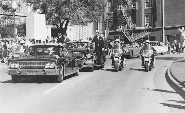 <p>Seen through the limousine's windshield as it proceeds along Elm Street past the Texas School Book Depository, President John F. Kennedy appears to raise his hand toward his head within seconds of being fatally shot in Dallas, Nov 22, 1963. Mrs. Jacqueline Kennedy holds the President's forearm in an effort to aid him. Gov. John Connally of Texas, who was in the front seat, was also shot. (Photo: Jim Altgens/AP) </p>