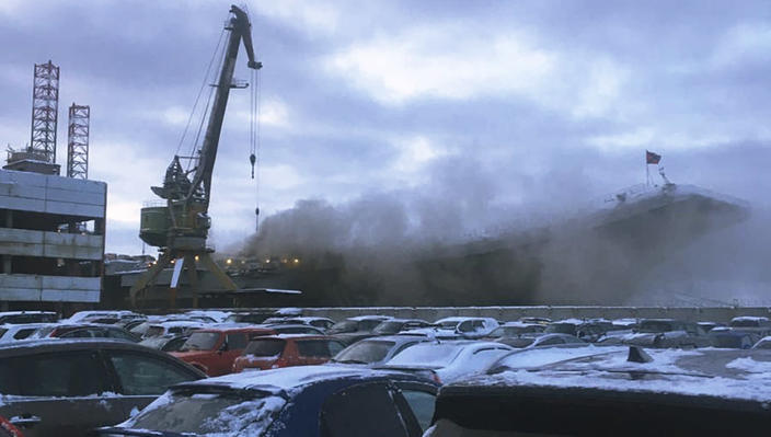 In this handout photo provided by an anonymous source, smoke billows from the Admiral Kuznetsov carrier during a fire in Murmansk, Russia, Thursday, Dec. 12, 2019. A fire on Russia's only aircraft carrier injured two service members, Russian military officials said Thursday. The Admiral Kuznetsov was docked in Murmansk in northern Russia for an upgrade when the fire started amid welding work on Thursday morning. (Anonymous Source via AP)