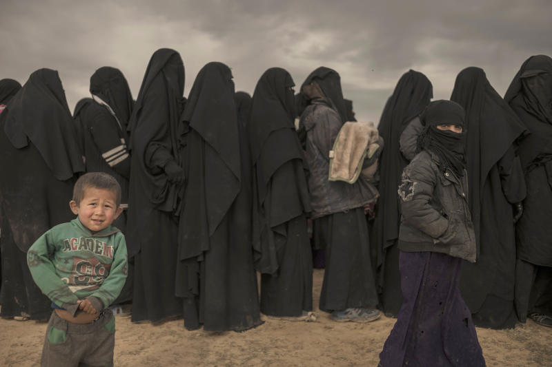 In this Wednesday, March 6, 2019, photo, women and children stand in line at a reception area for people evacuated from the last shred of territory held by Islamic State militants, outside Baghouz, Syria. (AP Photo/Gabriel Chaim)