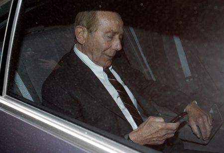 "Former CEO of American International Group Inc, Maurice ""Hank"" Greenberg, checks his phone inside a car after leaving a building in downtown New York where he was deposed by the Attorney General's office March 10, 2010.  REUTERS/Jessica Rinaldi"
