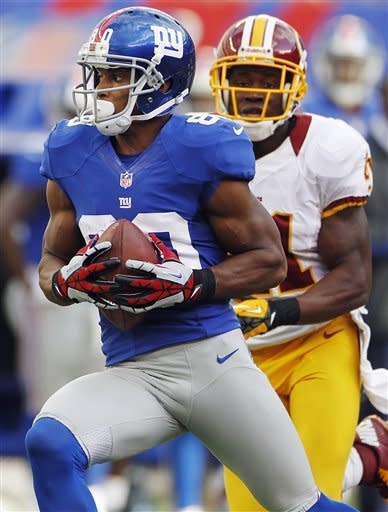 New York Giants wide receiver Victor Cruz (80) runs away from Washington Redskins' Madieu Williams (41) for a touchdown during the second half of an NFL football game, Sunday, Oct. 21, 2012, in East Rutherford, N.J. (AP Photo/Julio Cortez)