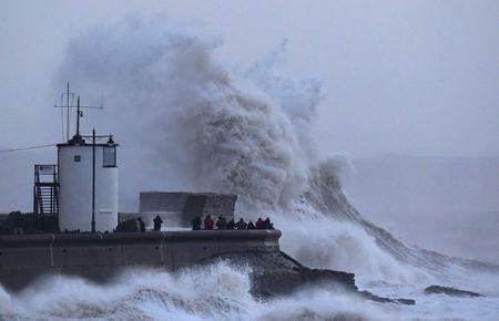 People view large waves and high winds associated with Storm Eleanor as they hit the lighthouse and seawall at Porthcawl in south Wales, Britain January 3, 2018.  REUTERS/Toby Melville