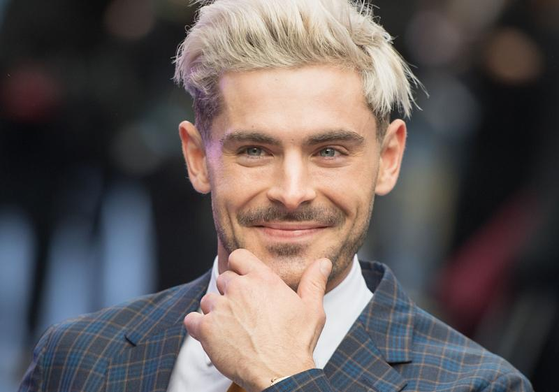 Zac Efron sports a striped two-piece suit with his signature blonde haircut