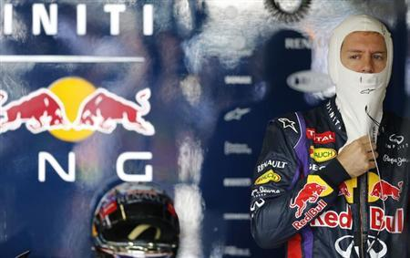 Red Bull Formula One driver Sebastian Vettel of Germany adjusts his balaclava during the third practice session of the Japanese F1 Grand Prix at the Suzuka circuit October 12, 2013. REUTERS/Issei Kato