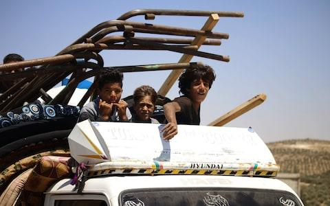 Young boys sit atop a truck as they flee rebel-held areas of the city of Daraa - Credit: MOHAMAD ABAZEED/AFP/Getty Images