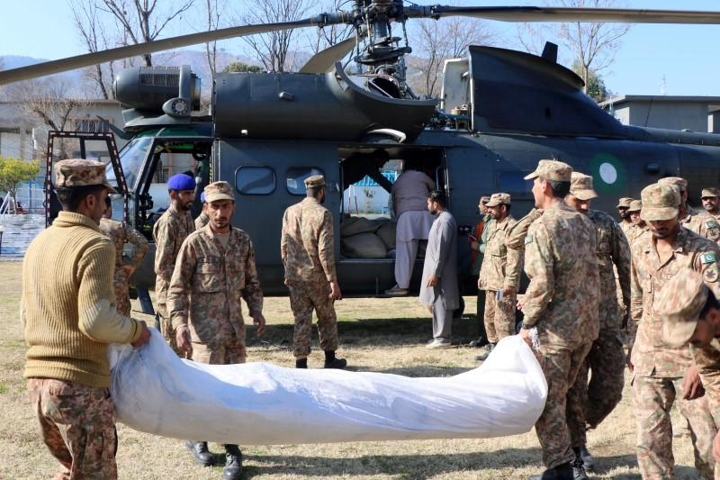 Pakistan Army soldiers load relief goods on a helicopter to distribute among people in affected areas after heavy snowfall and avalanches, in Muzaffarabad,