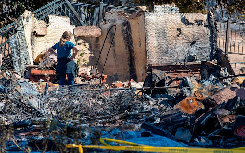 A family member of the homeowner stares at the rubble after the Hillside fire burned down from Highway 18 and Lower Waterman Canyon to this neighborhood on Saturn Court on October 31, 2019 in San Bernardino, California. | Gina Ferazzi/Getty Images