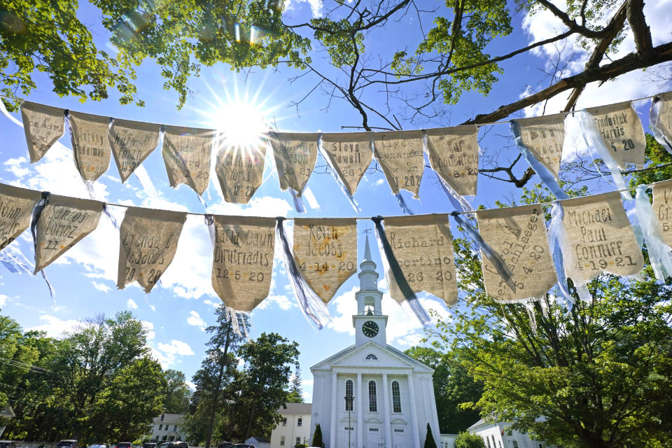 Flags with names of people who have died from COVID-19 are displayed outside the First Congressional Church, Thursday, June 17, 2021, in Holliston, Mass. The flags are part of the COVID Art and Remembrance project spearheaded by Jaclyn Winer, whose father, Keith Jacobs, died in April 2020 from the coronavirus. (AP Photo/Elise Amendola)
