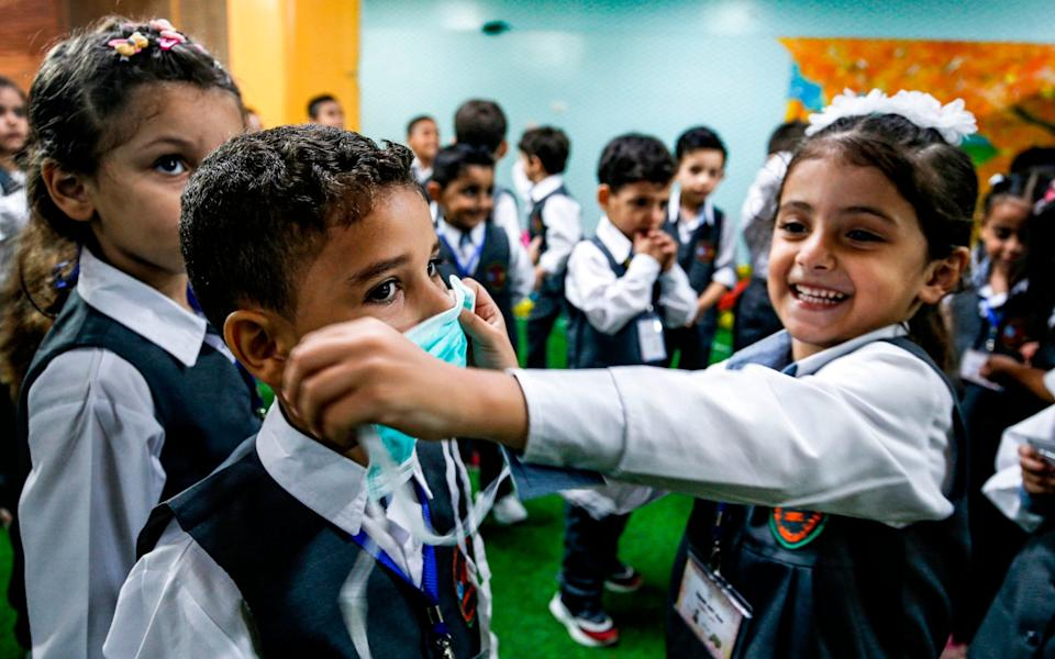 A girl applies a mask onto the face of another boy during an awareness session about Covid-19 coronavirus disease held by a local kindergarten in Gaza City - MOHAMMED ABED/AFP