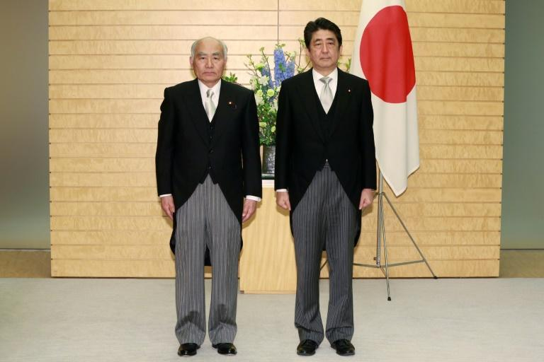 Japan's Prime Minister Shinzo Abe, right, stands with Masayoshi Yoshino, the newly appointed Minister for Reconstruction