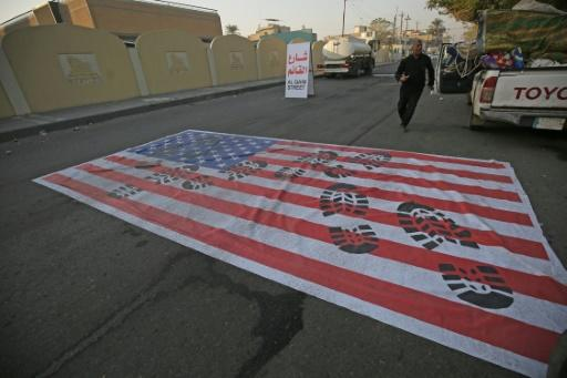 A mock US flag is laid on the ground for cars to drive over in the Iraqi capital Baghdad