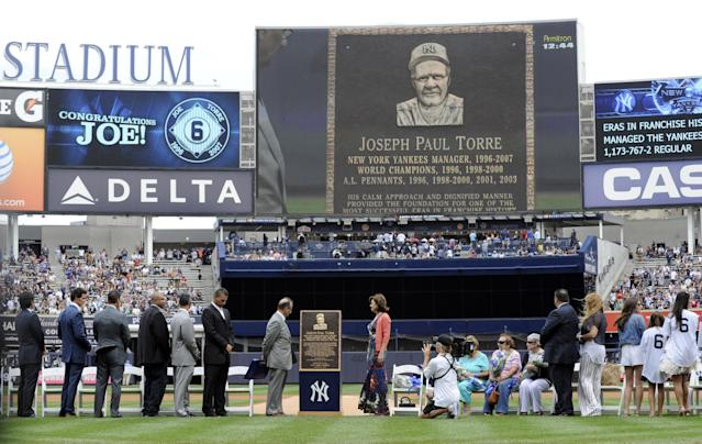 Former New York Yankees manager Joe Torre, center left, looks at a replica of his plaque that will hang in Monument Park as the Yankees retired his number before a baseball game against the Chicago White Sox Saturday, Aug. 23, 2014, at Yankee Stadium in New York. (AP Photo/Bill Kostroun)