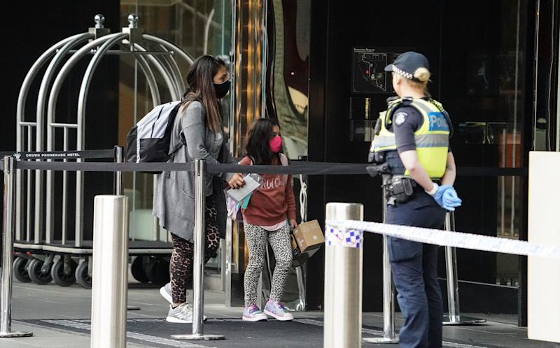 Recently arrived overseas travellers get off their bus and wait to check in at the Crown Promenade Hotel in Melbourne. Source: AAP