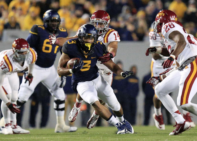 West Virginia running back Charles Sims (3) runs with the ball as several Iowa State defenders close in during the second half of an NCAA college football game against Iowa State in Morgantown, W.Va., on Saturday, Nov. 30, 2013. (AP Photo/Christopher Jackson)