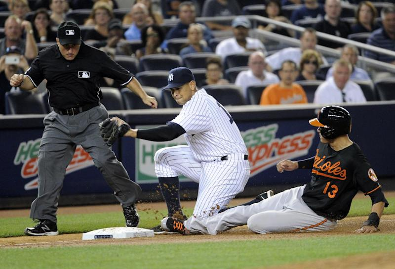 New York Yankees third baseman Alex Rodriguez, center, takes the throw as Baltimore Orioles' Manny Machado slides into third base on a wild pitch during the fourth inning of a baseball game while umpire Eric Cooper, left, looks on at Yankee Stadium, Friday, Aug. 30, 2013, in New York. (AP Photo/Bill Kostroun)