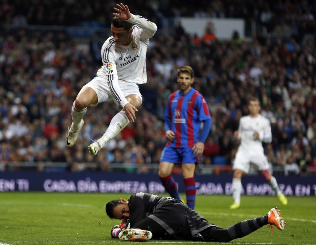 Real Madrid's Cristiano Ronaldo (L) jumps over Levante's goalkeeper Keylor Navas during their Spanish first division soccer match at Santiago Bernabeu stadium in Madrid March 9, 2014. REUTERS/Sergio Perez (SPAIN - Tags: SPORT SOCCER)