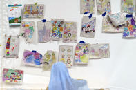 A child looks over artwork made by kids in a tent at Fort Bliss' Doña Ana Village, in New Mexico, where Afghan refugees are being housed, Friday, Sept. 10, 2021. The Biden administration provided the first public look inside the U.S. military base where Afghans airlifted out of Afghanistan are screened, amid questions about how the government is caring for the refugees and vetting them. (AP Photo/David Goldman)